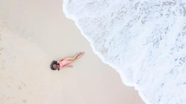 砂と波、日光浴と白い砂浜でリラックスした若い女性の上に横たわるビキニで空撮トップビュー若い女性