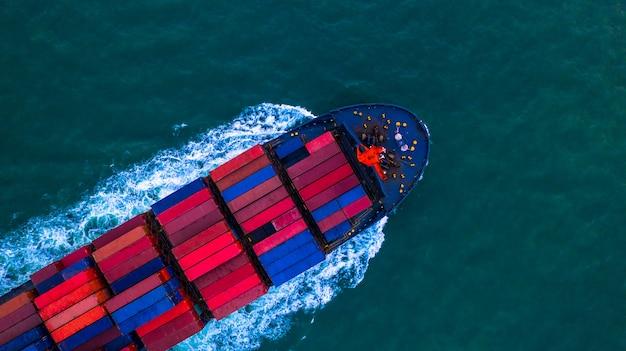 Контейнеровоз с контейнеровозом для импорта и экспорта бизнес логистики и транспортировки контейнеровозом в открытом море, вид с воздуха.