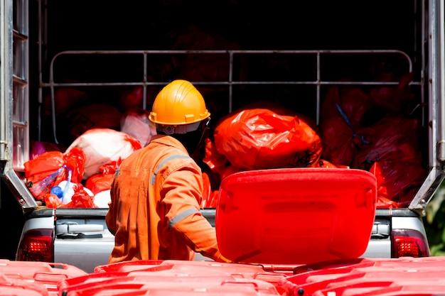 Человек в защитном костюме с красным мусорным баком и мешком для мусора.
