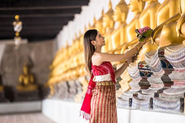 タイの寺院、タイのアイデンティティ文化の蓮を持っている伝統的なタイ衣装手でタイの女の子。