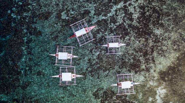 サンゴ礁に空撮伝統的なフィリピンのボート