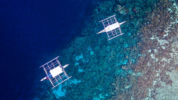 澄んだ青い海の上に浮かぶフィリピンのボートの空撮