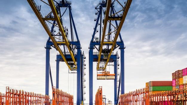 空撮貨物船ターミナル、貨物船ターミナルのアンロードクレーン、コンテナーとコンテナー船の空撮産業港。