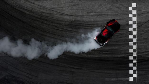 フィニッシュラインと燃えているタイヤからの煙の多いレーストラックで漂っている空中のトップビュー車。
