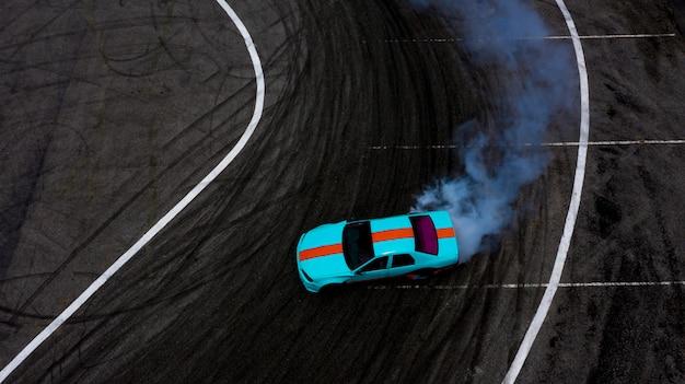 燃えているタイヤからの煙がたくさんあるアスファルトのレーストラックに漂う空中のトップビュー車。