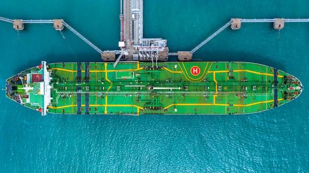 港の燃料タンカー船の空中のトップビュー、石油ターミナルは石油の貯蔵のための産業施設