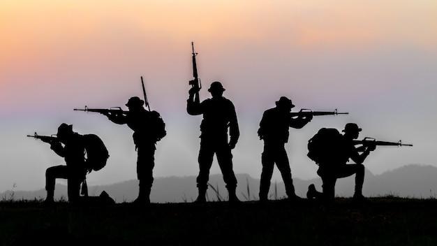 Воинские или солдатские силуэты на фоне закатного неба, полностью экипированный и вооруженный солдат, стоящий на силуэтах окружающей среды в закат.