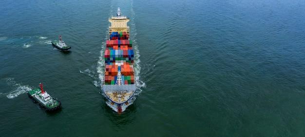 Контейнеровоз с аэрофотоснимком, несущий контейнерную коробку в экспорте импорта, грузовые перевозки глобального бизнеса, коммерческая логистика и транспортировка контейнеровозом по всему миру в открытом море.