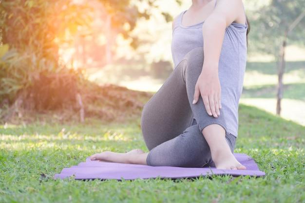 太陽の光と公園の緑の芝生の上でストレッチ運動をしている女の子