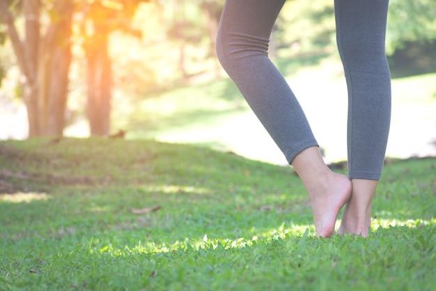 Девушка босиком стоя на зеленой траве в парке