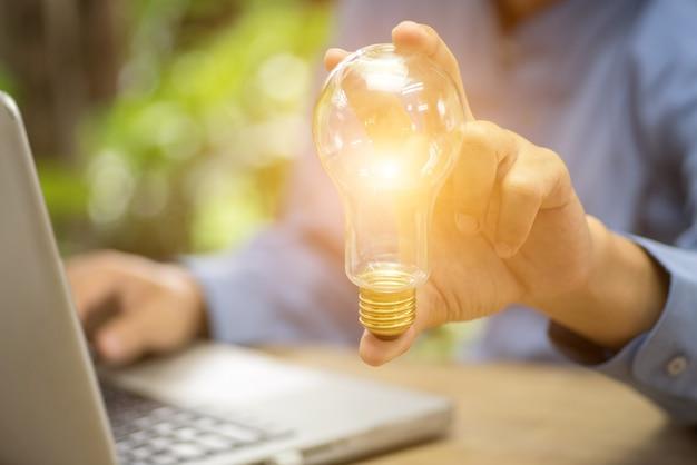 照明された電球、アイデア、革新とインスピレーションのコンセプトを保持しているビジネスマンの手