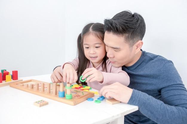お父さんと娘はおもちゃを一緒に遊んでいます。お父さんは娘におもちゃをブロックするように教えています。