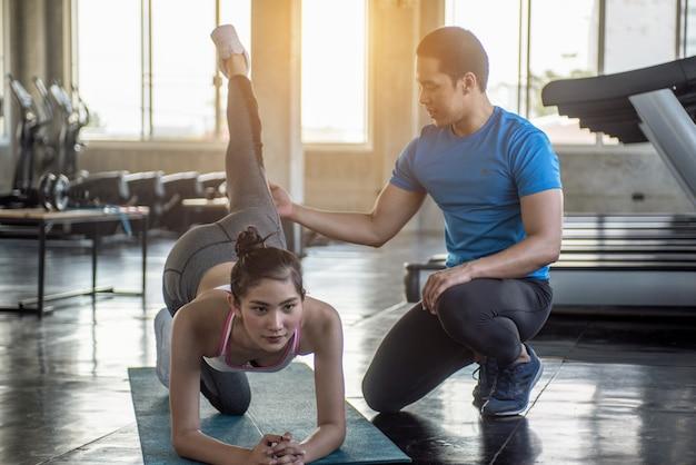 ヨガインストラクターは、初心者がストレッチ体操を行うのを助けます。先生がヨガのポーズを作るのを手伝います。