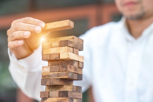 空の木製の立方体とピラミッドを作る実業家の拡大