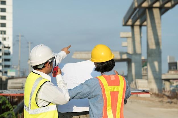 Строительный работник, проверяющий чертежи на месте