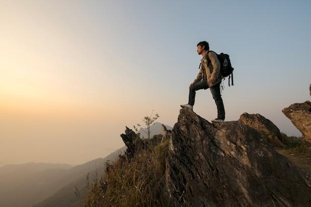 秋の霧の灰色の山の上に男性の観光客