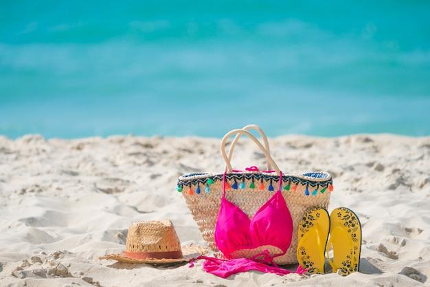 熱帯のビーチで麦わら帽子、サングラスバッグ、サンダル、ビキニ。