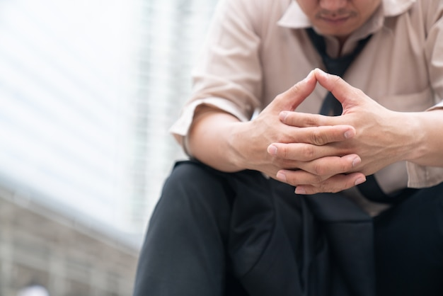 Усталый или подчеркнул бизнесмен, сидя на дорожке