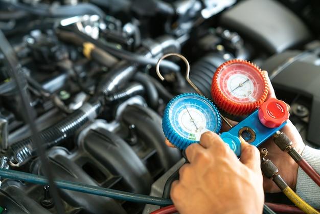 Инструмент мониторинга на автомобильном двигателе, готовый проверить и зафиксировать систему кондиционирования автомобиля в гараже автомобиля