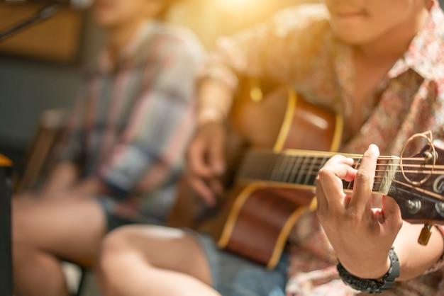 アコースティックギターを弾く男。断片。手に集中する