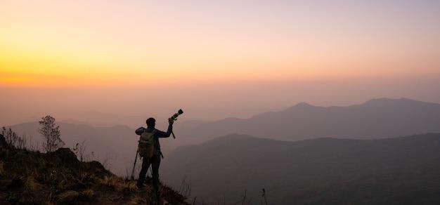 Фотограф празднует успех на вершине горы в величественном восходе солнца