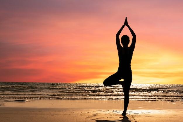 シルエットの若い女性が夕暮れ時のビーチでヨガを練習します。瞑想