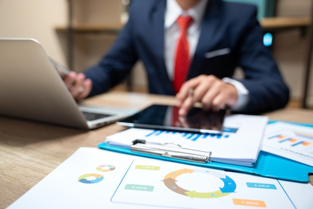 スマートフォンとデジタルタブレットのオフィスのテーブル上のビジネス文書