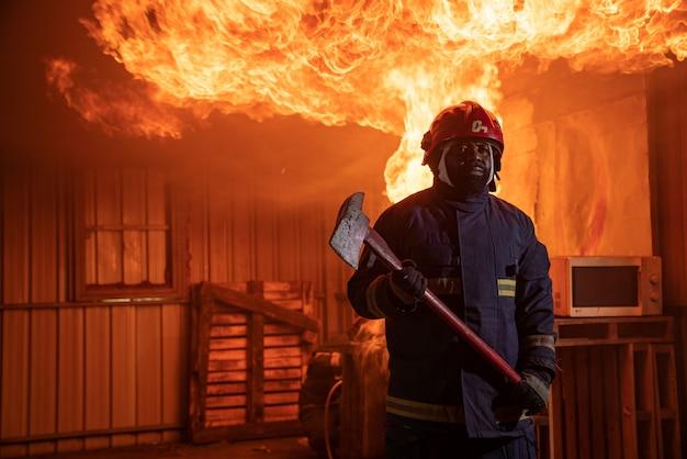 屋根の上の電線の前に制服とヘルメットを持つ消防士が立っています。