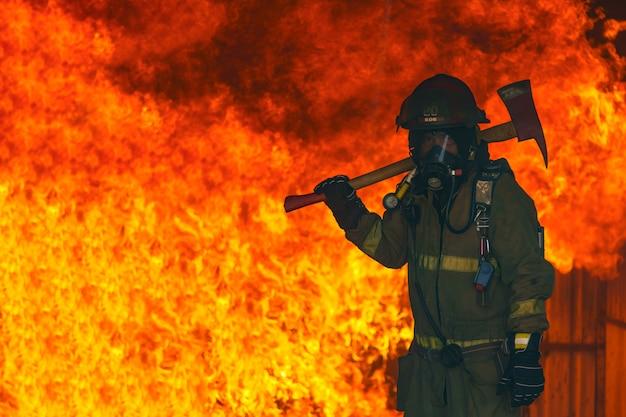 火の救助消防士男は鉄の斧を保持しています。