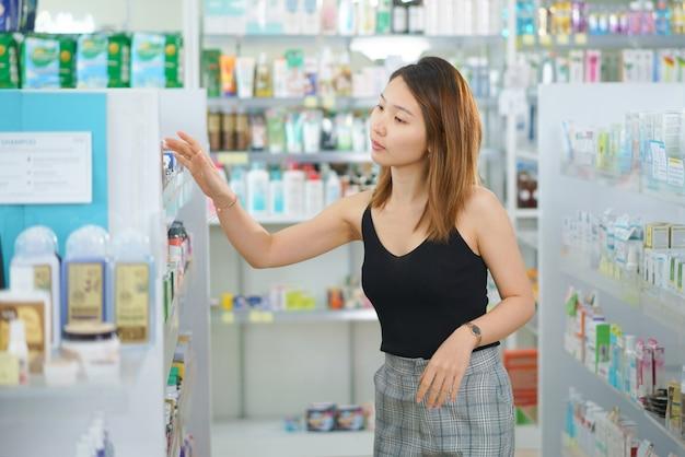 Молодая женщина сравнивает этикетки медицины в аптеке