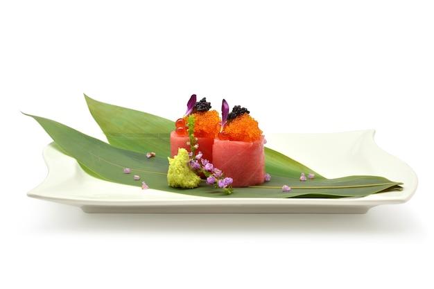 Отто-ролл специальный (икра, лососевая икра, магуро, отто) в белой тарелке на белом фоне
