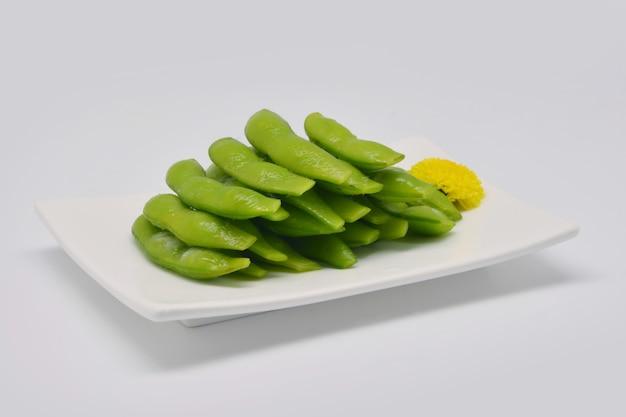 エダマメ、または白い背景の白い四角いプレートのエダマメ豆
