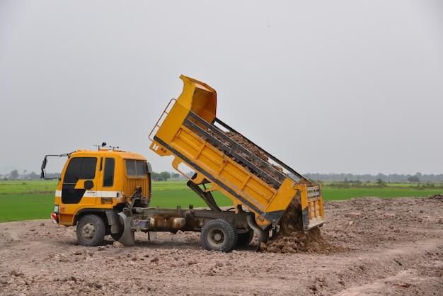 トラックは建設現場で土を捨てています