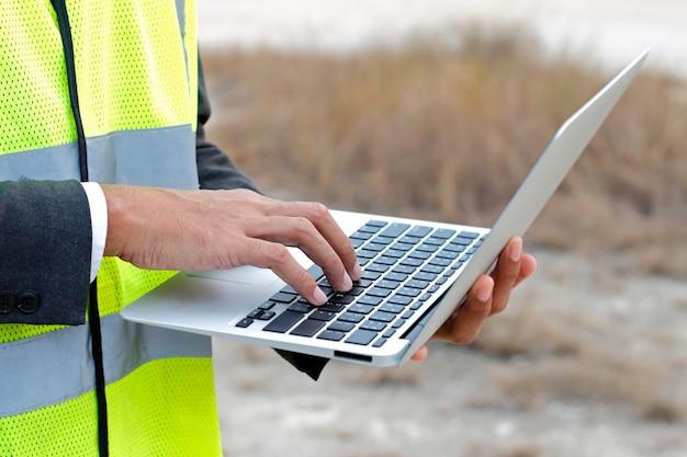 Инженер работает с ноутбуком на строительной площадке