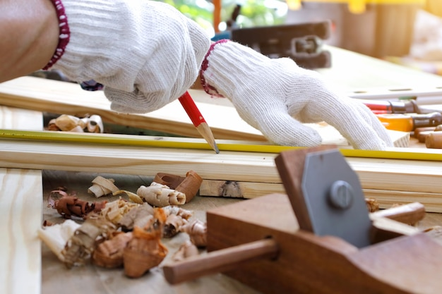 Плотник работает на деревообрабатывающей промышленности, держа на рабочем столе рулетку