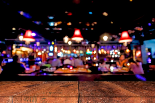 レストランライトの抽象的な背景をぼかした写真の前に木製のテーブル