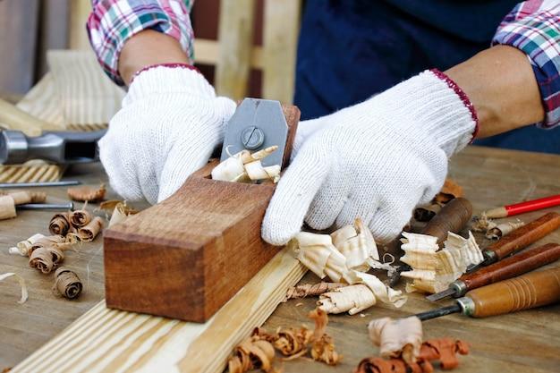 Плотник работает на деревообрабатывающем станке