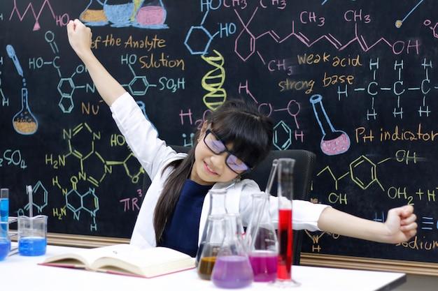 Маленькая девочка протягивая руки после делать эксперименты в лаборатории. наука и образование.