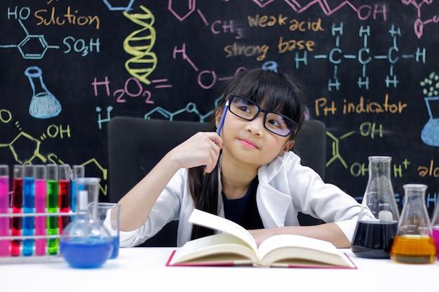 Маленькая девочка делает эксперименты с жидкостями в химической лаборатории. наука и образование.