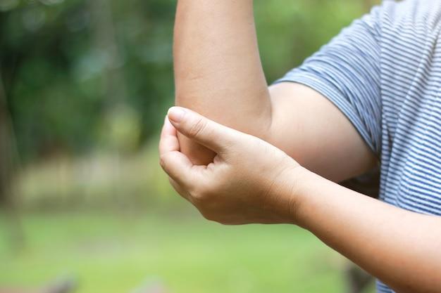 肘の痛みの場所に手を握って女性