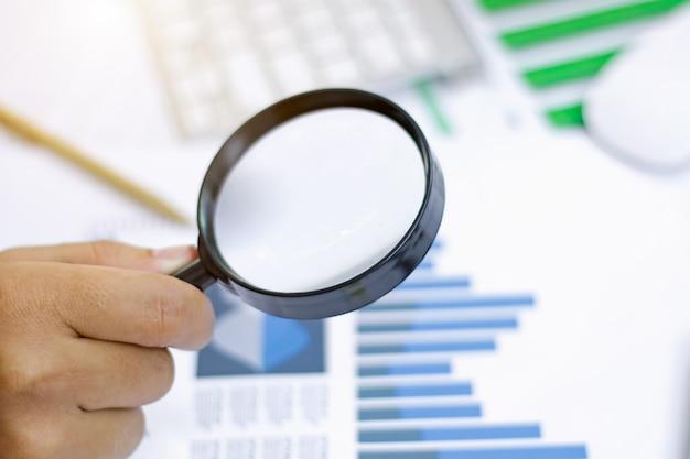 ビジネス分析と統計。株式市場のチャートに虫眼鏡を使用するビジネスマン