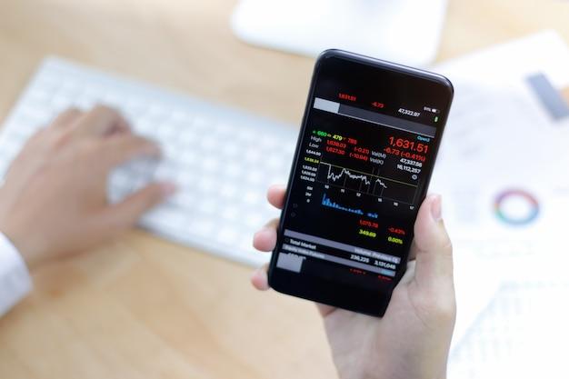 株式市場の傾向を示すスマートフォンを持っている手