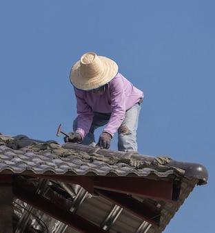 家屋の屋根瓦を設置する労働者