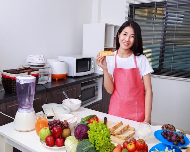 キッチンの部屋でパンを持っている女性