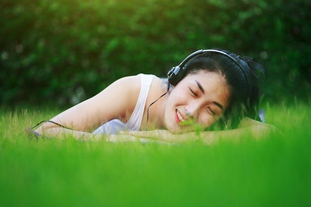 女性は、彼女の目が芝生のフィールドにヘッドホンで音楽を聴いている