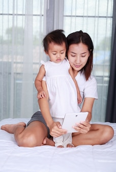 母親と赤ちゃんが家庭でタブレットコンピュータを再生して読んでみたい
