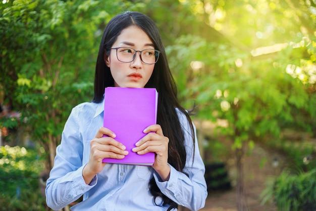 庭の本を持つ肖像画の女性