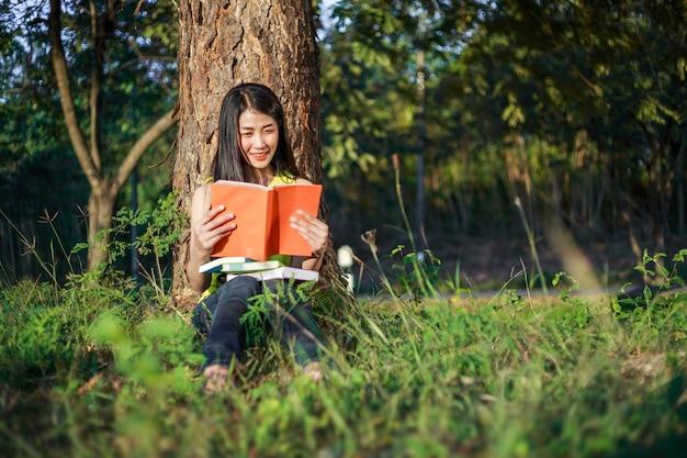座って公園で本を読む女性