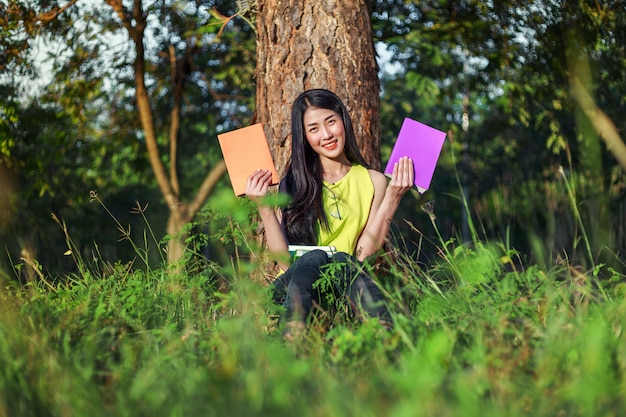 公園に座って本を持っている女性
