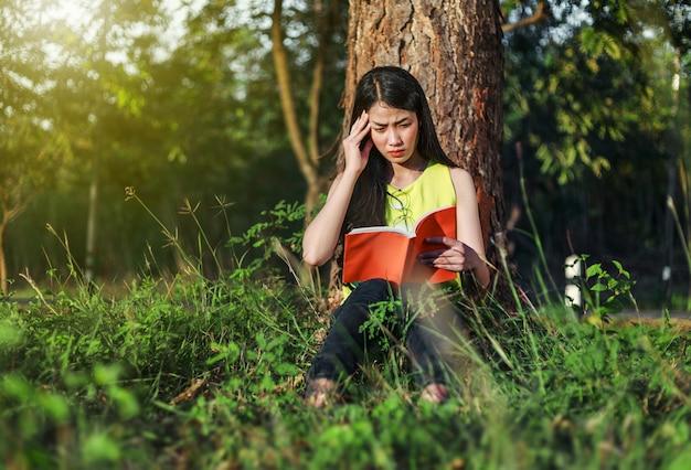公園で本を読むときのストレス状況にある女性